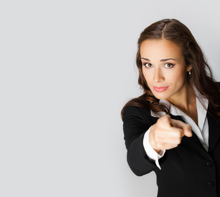 Portrait of young serious businesswoman pointing finger at viewer, with blank copyspace area for text or slogan photo