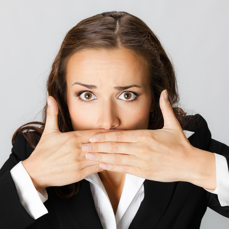 hand in mouth: Portrait of surprised excited young businesswoman covering with hands her mouth, against grey background
