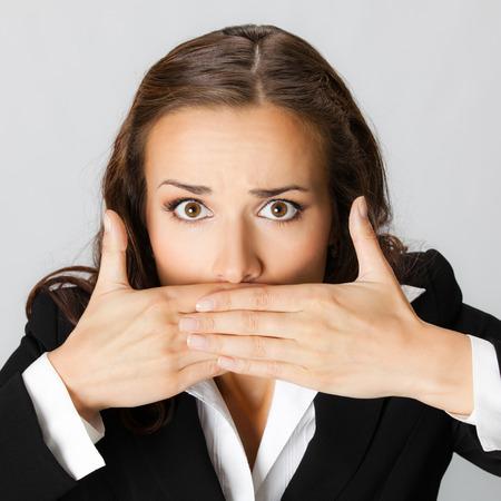 boca: Retrato de sorprendido joven empresaria emocionada con las manos cubriendo su boca, contra el fondo gris