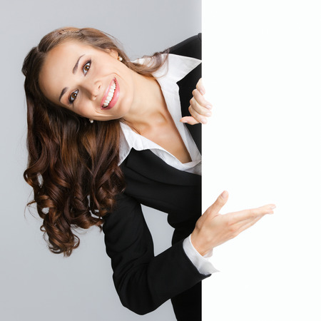 signboard: Cheerful businesswoman showing signboard with blank copyspace area for text or slogan
