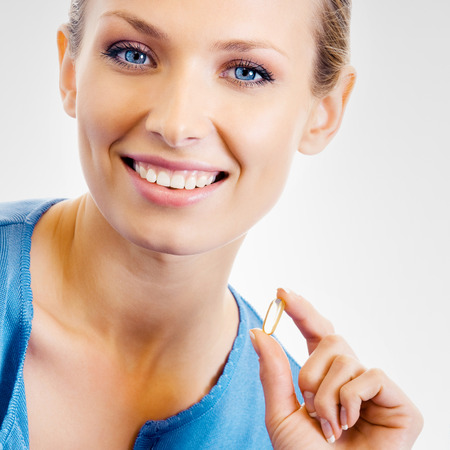 fish oil: Portrait of young woman with Omega 3 fish oil capsule, over grey background