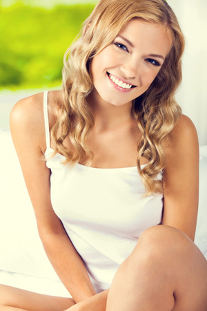 blondy: Portrait of smiling beautiful woman waking up, at bedroom Stock Photo