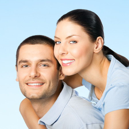Cheerful young smiling attractive couple, on blue sky background photo