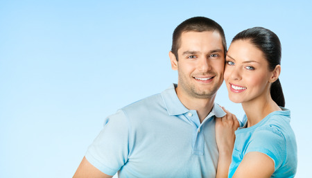 for text: Young happy smiling amorous attractive couple, against blue sky background, with blank copyspace area for text or slogan