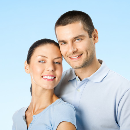 Cheerful young smiling amorous attractive couple, over blue sky background photo