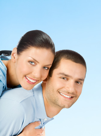 Cheerful smiling amorous couple, over blue sky background, with blank copyspace area for text or slogan photo