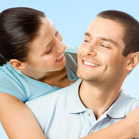 amorous: Happy young smiling amorous couple, against blue sky background