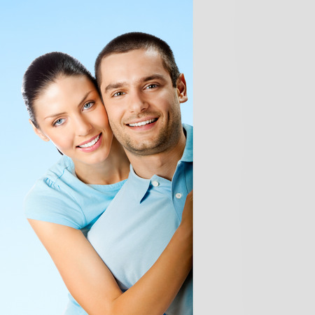 Young smiling amorous attractive couple, against blue sky background, showing blank signboard with copyspace area for text or slogan photo