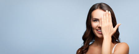 closed eye: Concept photo of happy smiling young woman with one eye, closed by hand, covering part of her face, over grey, with blank copyspace area for text or slogan
