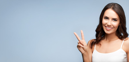 2 persons only: Portrait of beautiful young woman showing two fingers or victory gesture, on grey, with blank copyspace area for text or slogan
