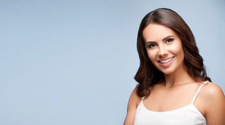 Portrait of beautiful cheerful smiling young woman, on grey, with blank copyspace area for text or slogan Stock Photo