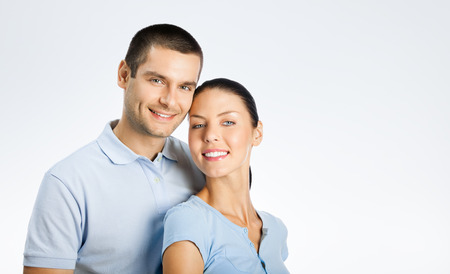 for text: Portrait of cheerful young couple, with copyspace blank area for text or slogan, over grey background