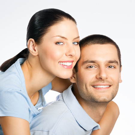 amorous: Portrait of cheerful smiling amorous young couple, over grey background Stock Photo