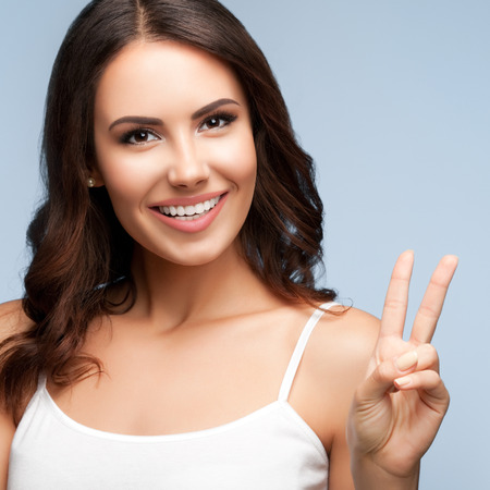 two persons only: Portrait of beautiful smiling young woman showing two fingers or victory gesture, on grey