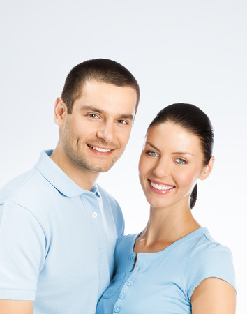 for text: Portrait of young happy smiling couple, with copyspace blank area for text or slogan, over grey background