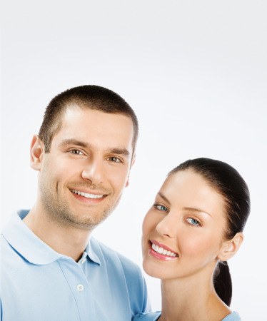 for text: Portrait of happy young couple, with copyspace blank area for text or slogan, on grey background
