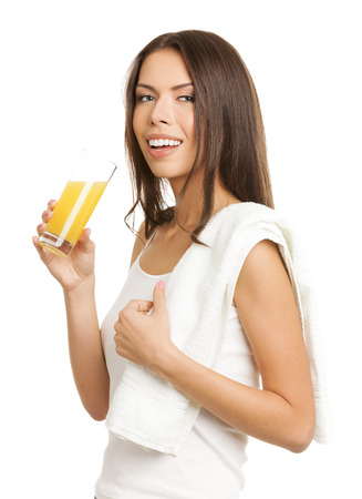 Portrait of young happy smiling brunette woman drinking fresh lemon or orange citrus juice, in tank top casual smart clothing, isolated over white background. Healthy lifestyle and dieting concept. photo