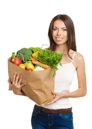 Portrait of happy smiling young woman holding grocery shopping bag with healthy vegetarian raw food, in tank top casual clothing, isolated on white background. Healthy eating and dieting concept. photo
