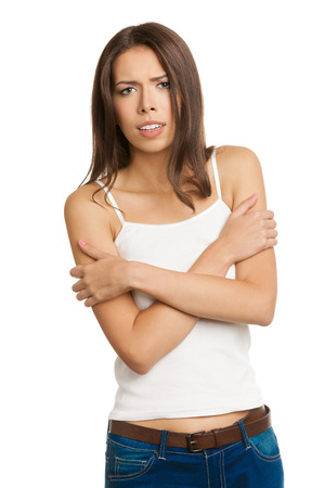 trembling: Portrait of trembling or freezing young brunette woman feels cold, with crossed arms, in tank top casual smart clothing, isolated over white background. Negative and stress emotions concept.