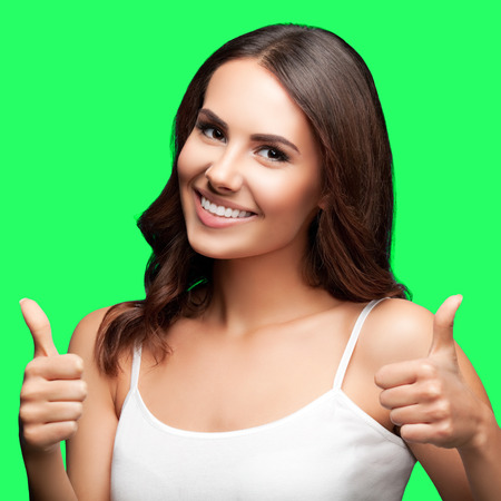 thumb keys: Portrait of happy smiling young beautiful woman in white casual clothing, showing thumbs up gesture, isolated over green screen chroma key background