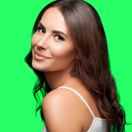 Portrait of happy smiling young beautiful woman in white casual clothing, isolated over green screen chroma key background photo