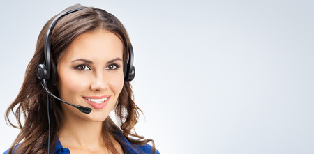 online support: Portrait of happy smiling young support phone operator or businesswomen in headset, with blank copyspace area for slogan or text Stock Photo