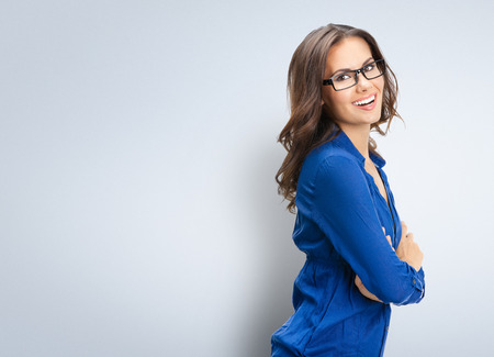 Portrait of smiling young businesswoman in glasses, with blank copyspace area for slogan or text