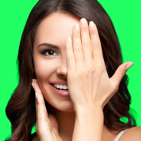 closed eye: Concept photo of happy smiling young woman with one eye, closed by hand, covering part of her face, isolated over green screen chroma key background Stock Photo