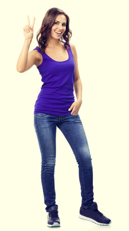 2 persons only: Full body portrait of happy smiling beautiful young woman in violet smart casual clothing, showing two fingers or victory hand sign gesture