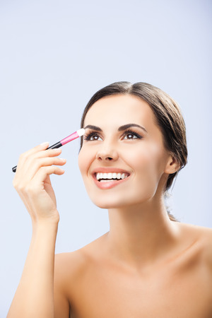 Young happy smiling woman with cosmetics brush, over grey background photo