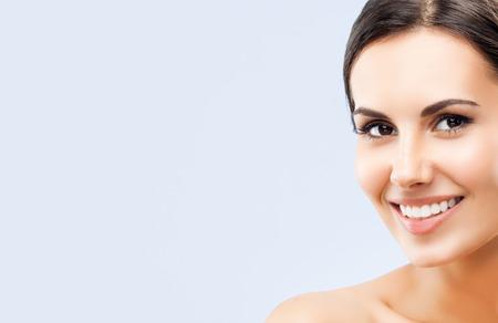 desnuda: Retrato de una hermosa joven feliz sonriente mujer morena, con los hombros desnudos, sobre fondo gris, con �rea vac�a en blanco copyspace para lema o texto