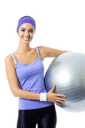 Portrait of happy smiling woman holding fitness pilates ball, in violet sportswear, isolated over white background. Young sporty dark-haired model at studio shot. Health, beauty and fitness concept. photo