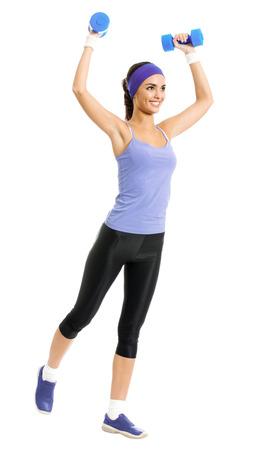 ropa deportiva: Todo el cuerpo de la mujer sonriente feliz en ropa deportiva violeta, haciendo ejercicio físico con pesas, aislado sobre fondo blanco. Modelo de pelo oscuro deportiva joven en tiro del estudio. Salud, belleza y el concepto de fitness. Foto de archivo