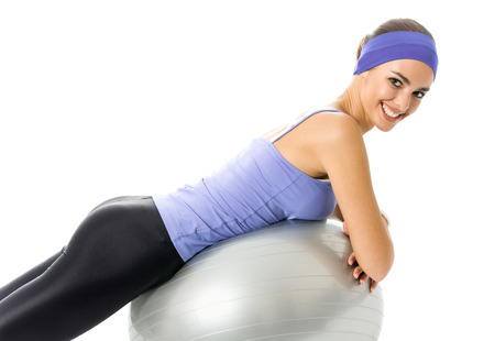 Happy smiling woman in violet sportswear, doing fitness exercise on pilates ball, isolated on white background. Young sporty dark-haired model at studio shot. Health, beauty and fitness concept. photo