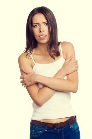 tremante: Tremando o congelamento giovane donna si sente freddo, con le braccia incrociate, in canotta abbigliamento casual. Concetto negativo e le emozioni di stress.