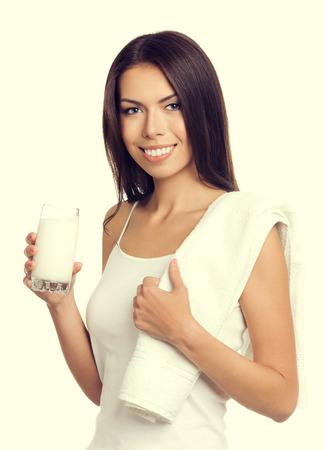 tomando leche: Retrato de joven alegre leche de consumo mujer morena, en camiseta de tirantes ropa informal elegante. Estilo de vida saludable y el concepto de dieta. Foto de archivo