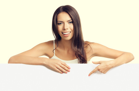 empty tank: beautiful young brunette woman in tank top casual smart clothing, pointing on empty blank signboard with copyspace area for text or slogan
