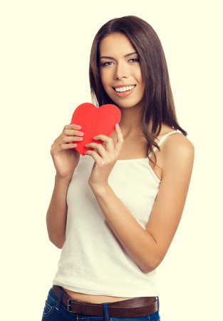 likeness: Portrait of cheerful young brunette woman in tank top casual smart clothing, showing red heart shape symbol. Valentines day and love concept. Stock Photo