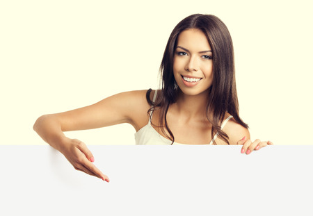 empty tank: Beautiful young brunette woman in tank top casual smart clothing, showing empty blank signboard with copyspace area for text or slogan