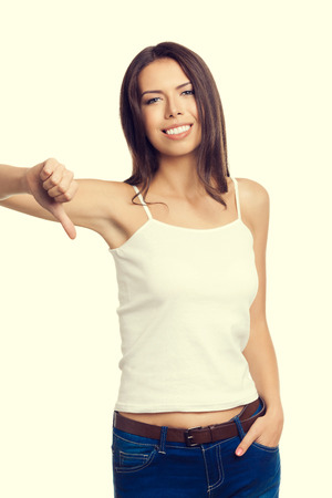 rejection sad: Portrait of cheerful young woman in tank top casual smart clothing showing thumb down hand sign gesture. Disapproval and negative reject reaction concept.