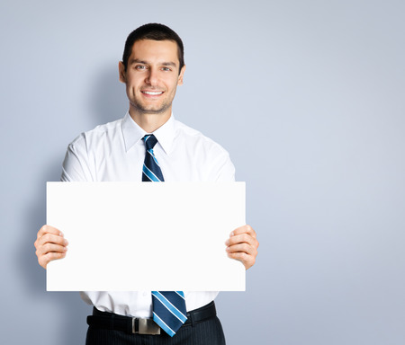 Portrait of happy smiling young businessman showing signboard, against grey background. Copyspace blank area for slogan or text. Business and success concept. Stockfoto