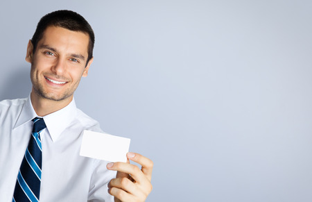 debet: Portrait of smiling businessman showing blank business or plastic credit card, against grey background. Copyspace blank area for slogan or text. Business and success concept.