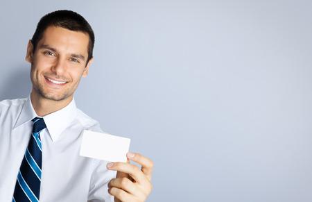 tarjeta de credito: Retrato de hombre de negocios sonriente que muestra en blanco negocio o tarjeta de crédito de plástico, sobre fondo gris. Copyspace área en blanco para lema o texto. Negocios y el concepto de éxito.