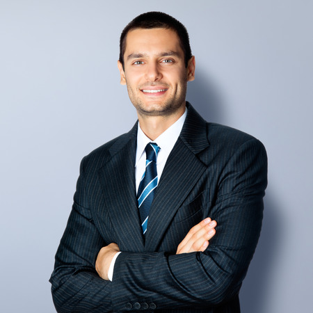 modelo: Retrato de hombre de negocios sonriente feliz en los brazos cruzados pose, en traje negro confianza, contra el fondo gris. Modelo masculino cauc�sico en tiro del estudio. Negocios y el concepto de �xito.