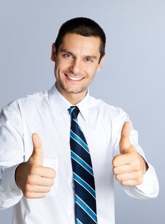 thumbup: Portrait of happy smiling businessman showing thumbs up hand sign gesture, against grey background. Caucasian male model at studio shot. Business and success concept.
