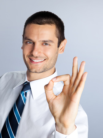 Happy smiling businessman showing okay hand sign gesture, against grey background. Caucasian male model at studio shot. Business and success concept. photo