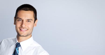 slogan: Retrato de hombre de negocios alegre, contra el fondo gris. Copyspace �rea en blanco para lema o texto. Modelo masculino cauc�sico en tiro del estudio. Negocios y el concepto de �xito. Foto de archivo