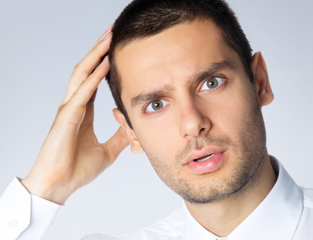 Portrait of shocked puzzled or pensive businessman, over grey background. Caucasian male model at studio shot. Business idea concept. photo