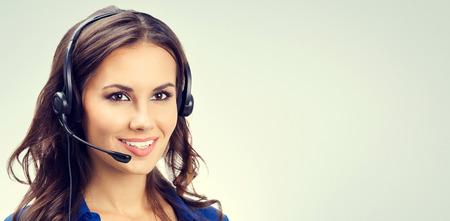 persona feliz: Alegre sonriente joven operador de soporte telefónico o empresarias en auriculares, con área de copyspace en blanco para lema o texto. Concepto de servicio al cliente.