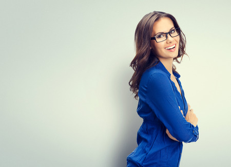 anteojos: Alegre sonriente joven empresaria en gafas, con área de copyspace en blanco para lema o texto